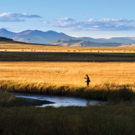 Fisherman on a river in a prairie