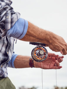 Close-up of an angler's hands and a reel on a fly rod