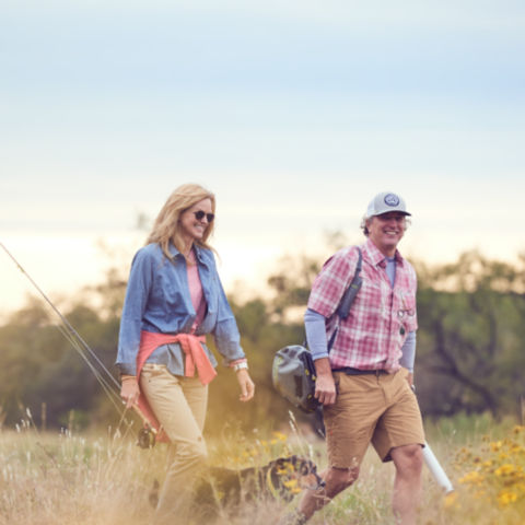 Couple walking through a field with their dog