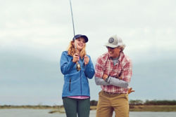 father teaching his daughter how to cast a fly rod