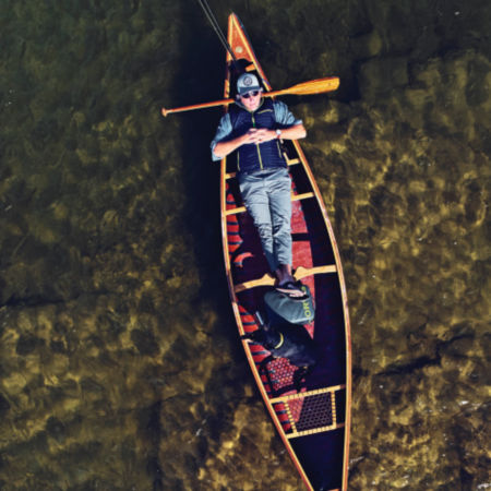 A man laying in a canoe
