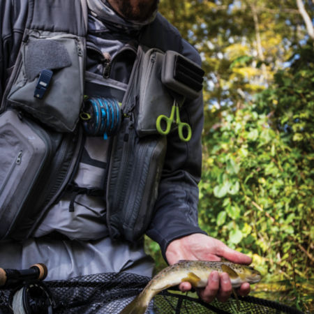 A close-up of an angler wearing a loaded fishing vest holds a trout above thier net..