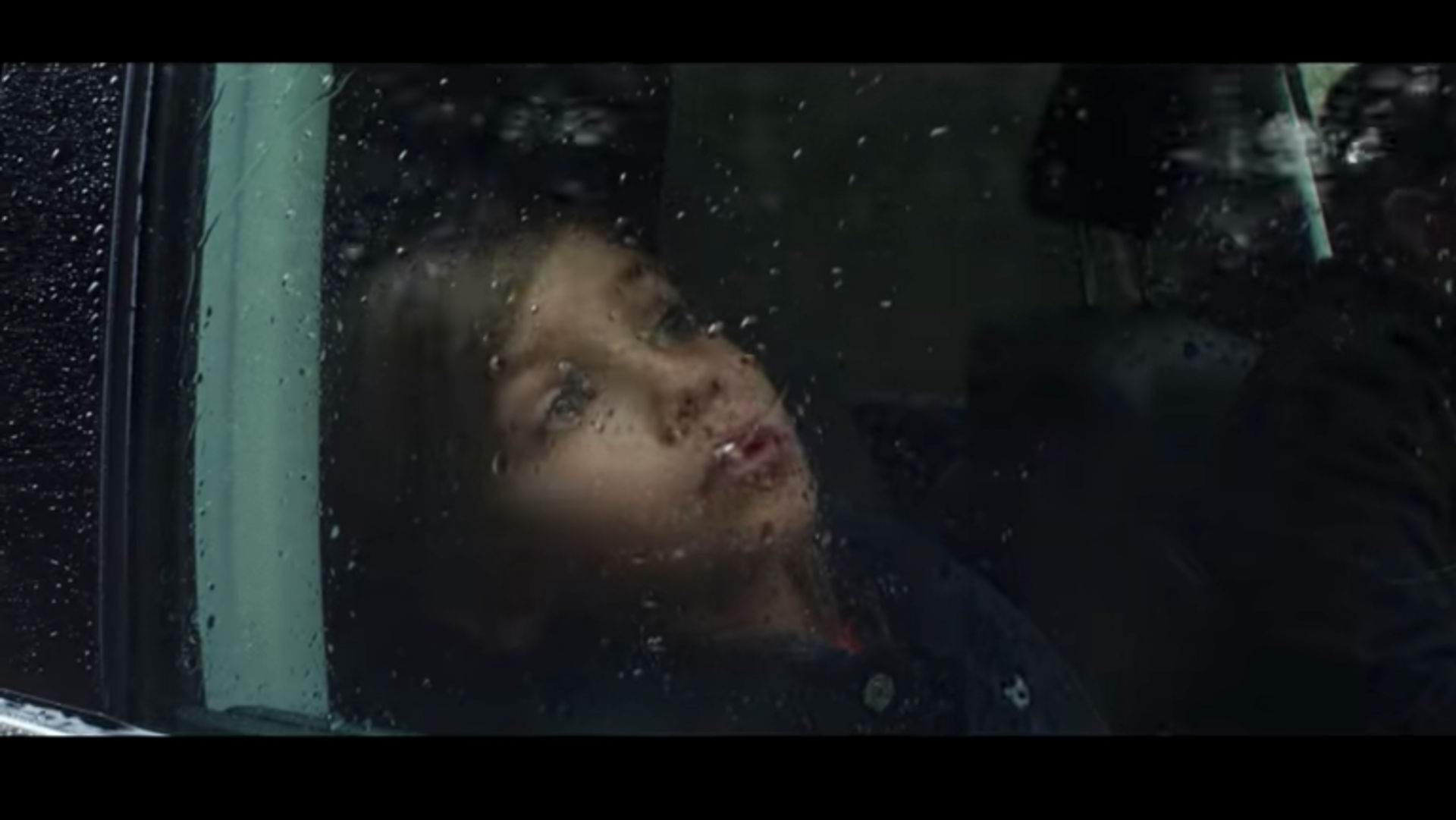 A girl looking out a rain covered window