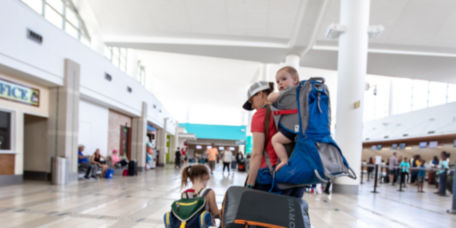 A woman walking through an airport with children and Orvis Luggage