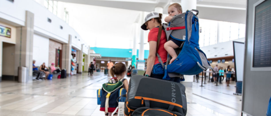 Woman and children walking with bags through airport