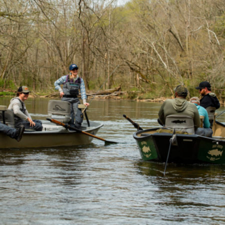 A group of anglers in two boats floating in a river