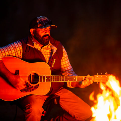 A guitarist playing around the campfire