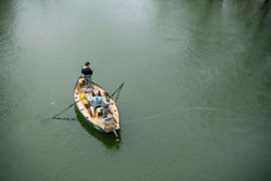 Two anglers cast from either end of a boat on the river.