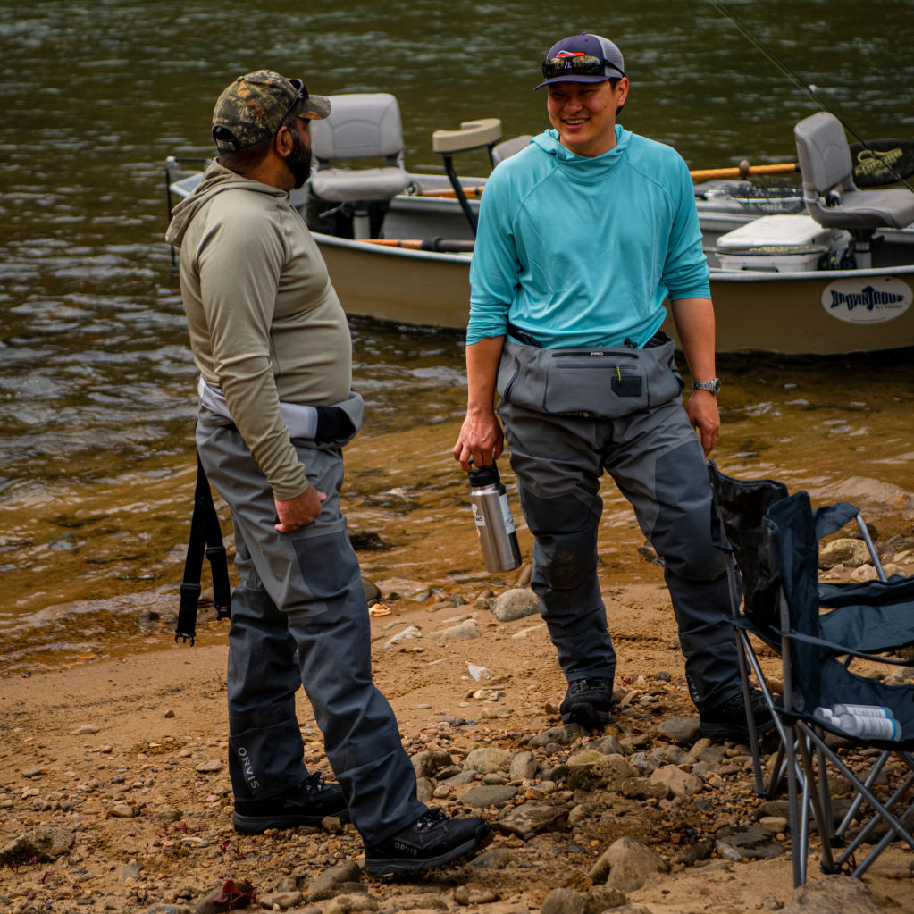 Two friends in fly-fishing gear catching up by a river
