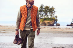 Man in orange vest holding a pair of boots