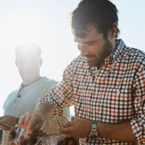 Man tying meat on a spit wearing a Wrinkle-Free shirt.