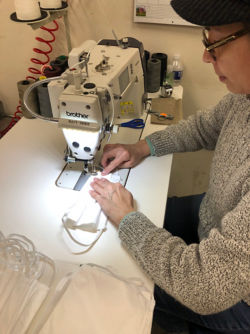 Woman at a sewing machine making a COVID-19 mask.