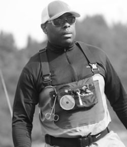 Black and white photo of Chad Brown wearing fishing gear