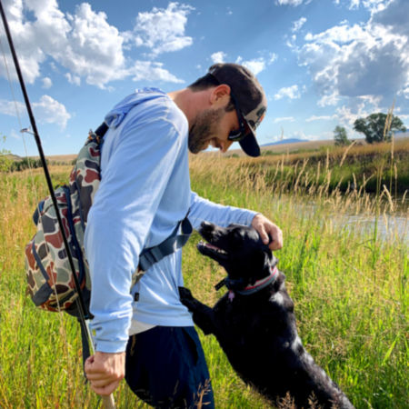 Charlie Perkins petting his dog Romy in a green, grassy field