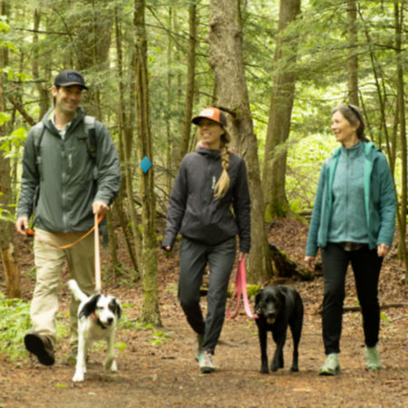 Man and woman hiking with dog