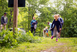 little girl running ahead of her family outside