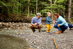 parents and children exploring a riverbank in the woods