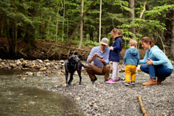 family exploring at the edge of a river