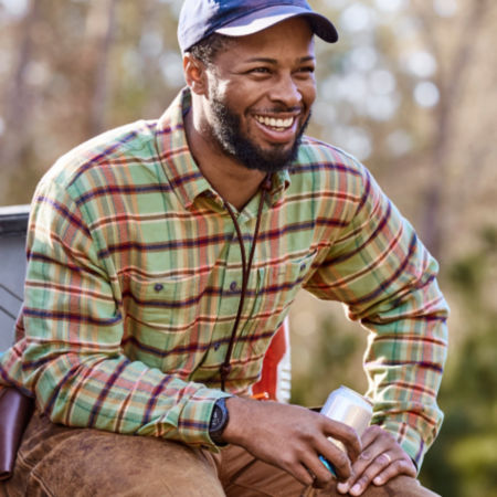 Durrell Smith, wearing a green plaid shirt, smiles as he holds a drink.