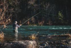 An angler wades waist-deep in a shallower spot of a deep river.