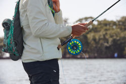 An angler wearing a brightly patterned fishing pack steadies their fly rod against their hip.