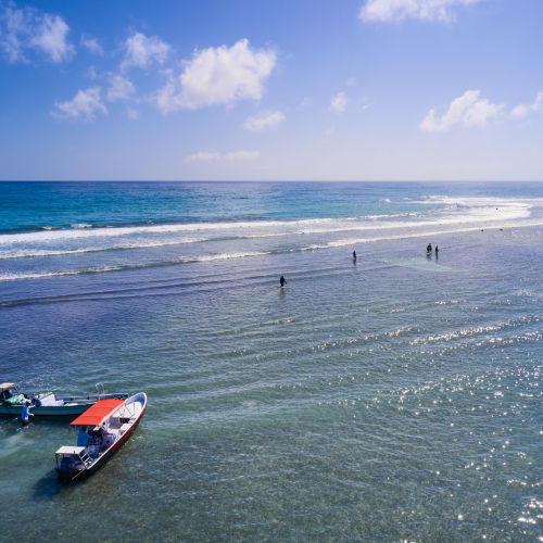 Drone view of the coastline with bright boats and fishermen