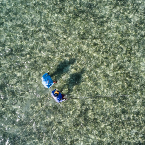 View from drone looking down on 2 fishermen in the water