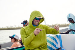 An angler wearing a PRO Sun hoodie measures out some line while holding the end in their teeth.