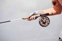 A gloved angler holds a Helios 3 rod with a large-arbor Mirage LT reel.