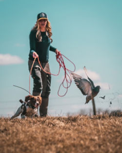 Woman holding the leash of a dog charging after a bird