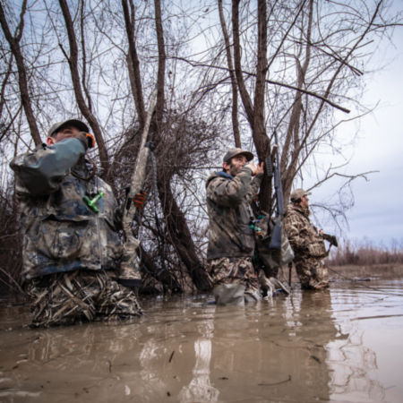 Three camouflaged hunters standing along the brush, sounding their bird calls.