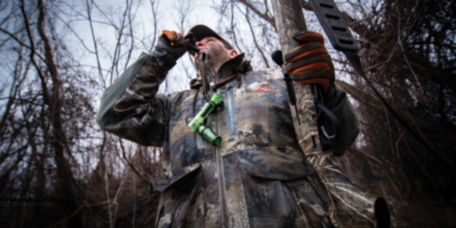 A hunter in camouflage blows a bird call.