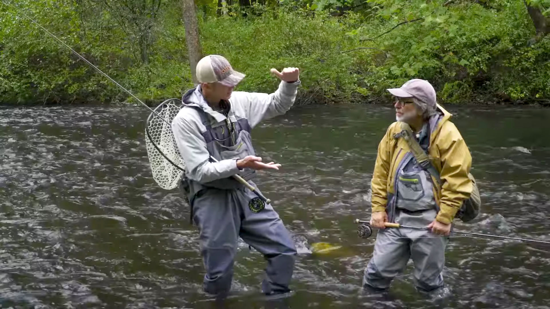 George Daniel uses his hands to indicate about of foot of distance to Tom Rosenbauer as they both wade knee-deep in the river.