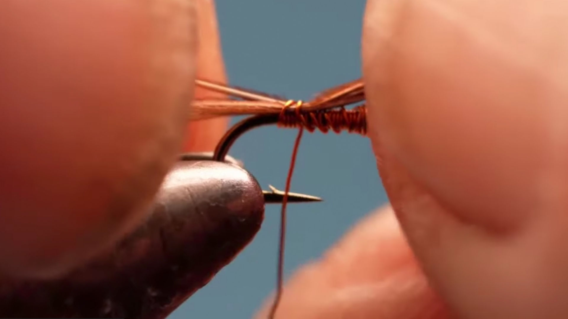 AN extreme close-up of fingers tying a fly on a vice.