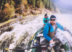 Two excited anglers in a raft riding over some rapids.