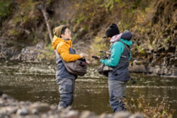 Two anglers stand face to face in the river