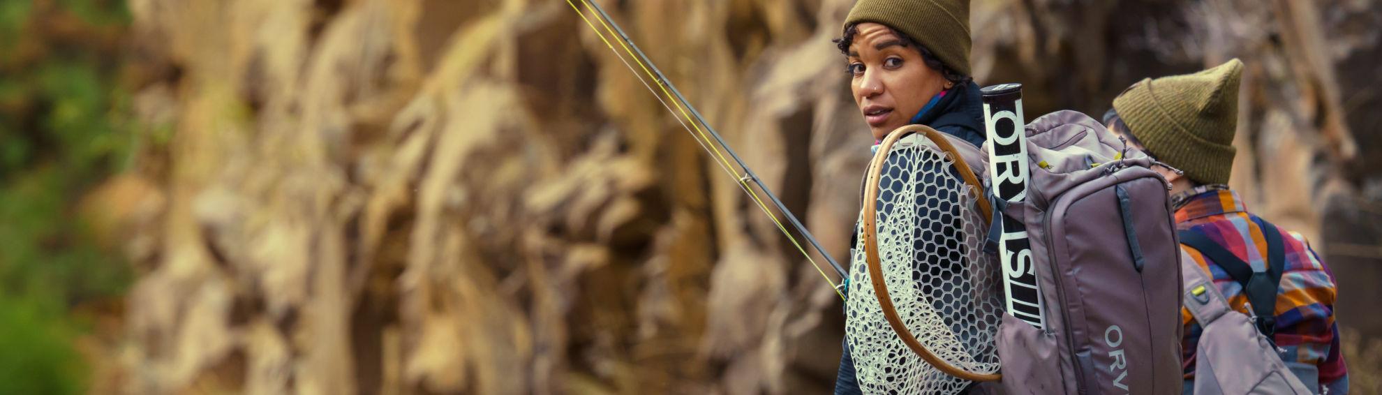 Woman fishing wearing a fishing pack