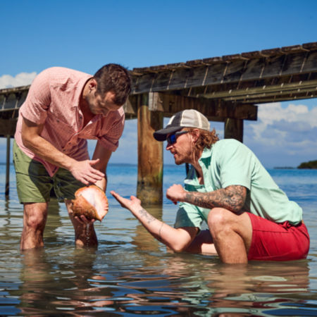 Two men wet wading near a wooden bridge inspect a large seashell.