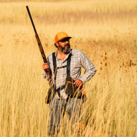 A hunter carrying a shotgun through an upland field