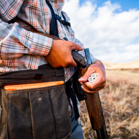 A hunter takes two shotgun shells out of their vest.
