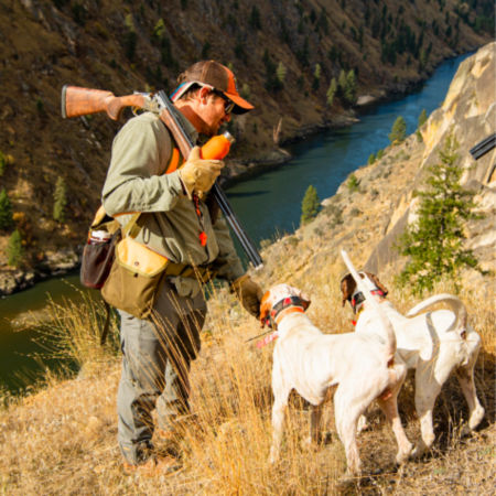 A hunter and their two dogs on a steep hill with the river below.