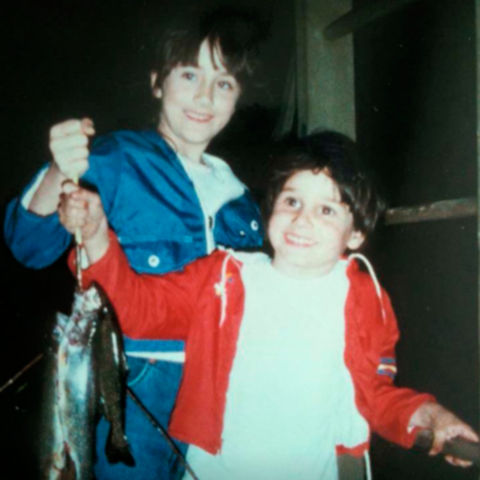 Young Jeff and his older sister hold up several fish they caught.