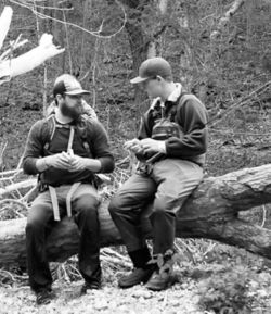Black and white image of Jess and a friend in the woods wearing waders