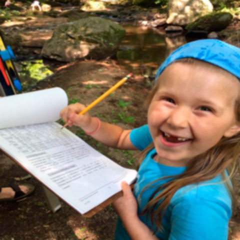 A young girl smiles while filling out records on a clipboard.