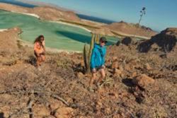 Two women hiking in the desert with a lake in the background