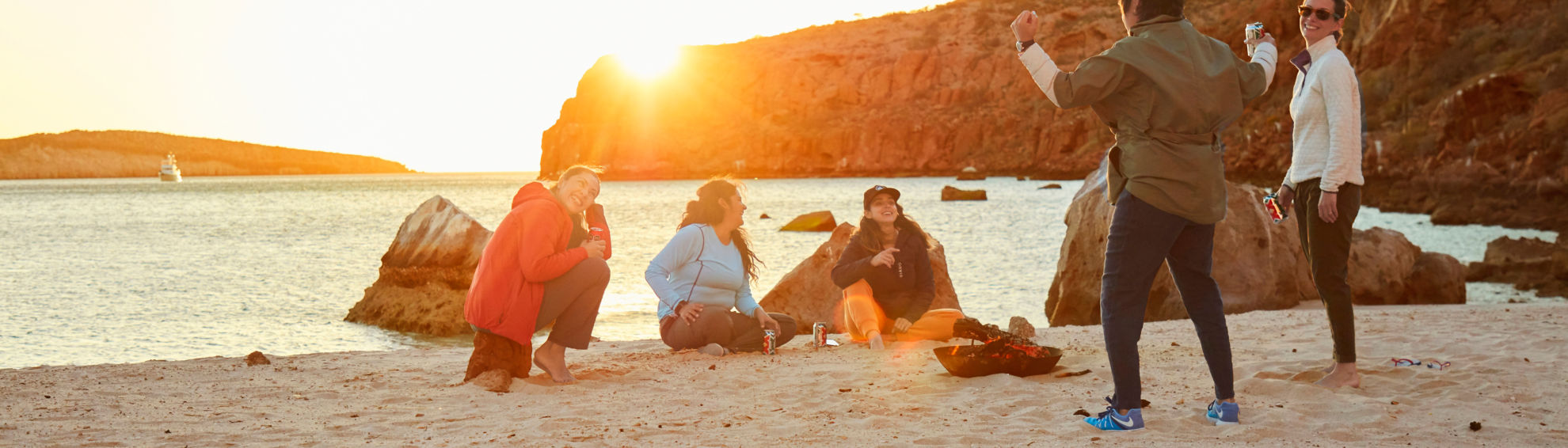 a group of women enjoying the sunset and lively conversation on a beach