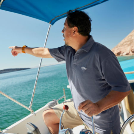 A fisherman pointing out of a boat across the water