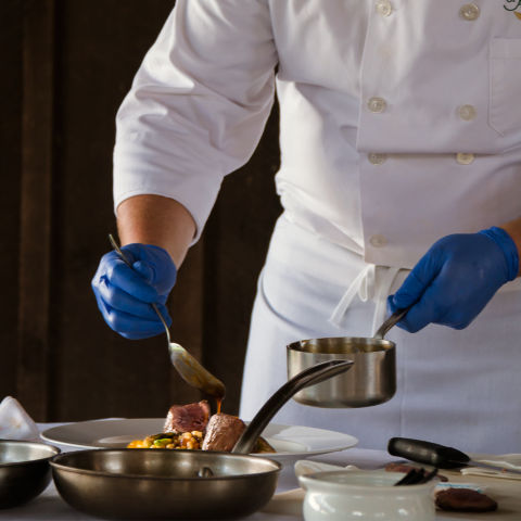 Chef wearing white demonstrating game cooking