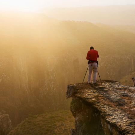 Man taking photos off a cliff