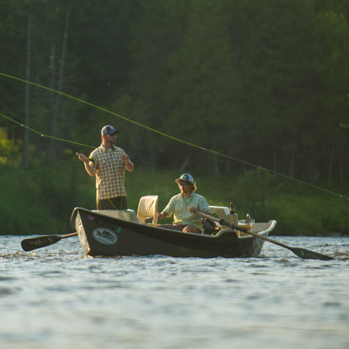 two men on a boat fishing in lake